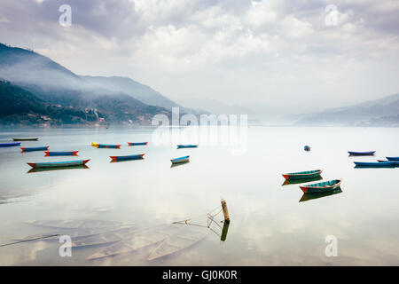 Boats on Phewa Lake in Pokhara, three sunken ones in the foreground, Nepal. - Stock Photo