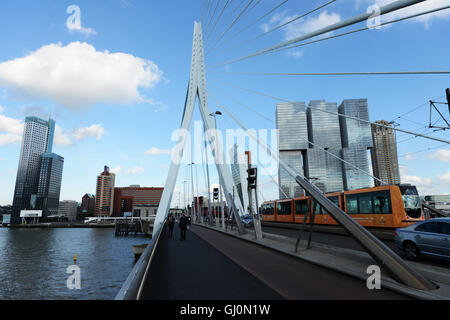 A tram crossing the Erasmus bridge over the Maas river with the De Rotterdam building in the background. - Stock Photo