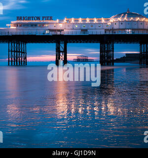 Brighton Pier at dusk reflects in the wet sands of low tide. In the distance the old West Pier can be seen. - Stock Photo