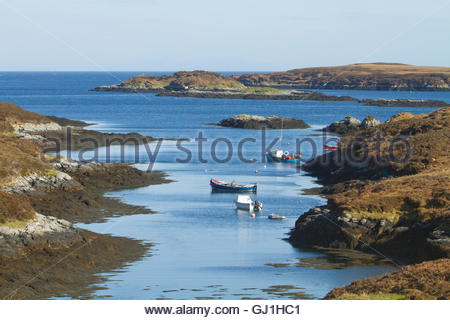 Small boats moored at Eilean na Cille on the east coast of the Isle of Benbecula, Outer Hebrides, Scotland. - Stock Photo
