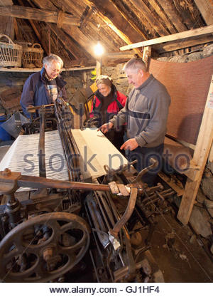 A weaver demonstrates a loom to two visitors at the Gearrannan Blackhouse Village, Carloway, Isle of Lewis, Outer - Stock Photo