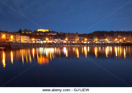 The view across the bay towards McCaig's Tower at dusk, Oban, Argyll, Scotland. - Stock Photo