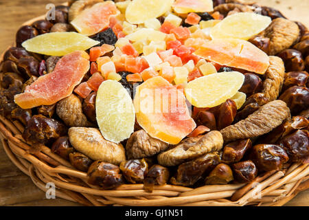 Dried and candied fruits assortment in a wicker tray - Stock Photo