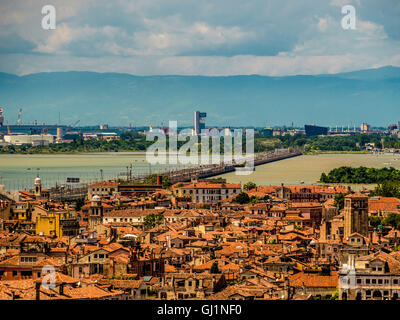 Aerial view of terracotta roofs, with the road and railway line from mainland Italy in the distance. Venice, Italy. - Stock Photo