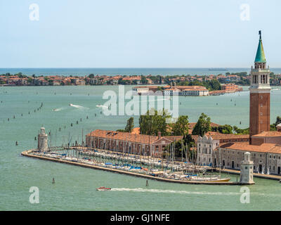 San Giorgio Maggiore harbour and bell tower with the island of San Servolo, home to Venice international University - Stock Photo