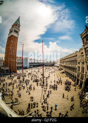 Fisheye shot from the loggia or balacony of St Mark's Basilica, of the tourist packed square below and nearby bell - Stock Photo