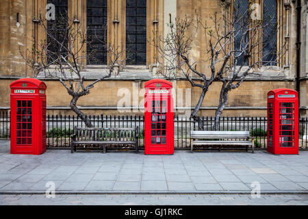 Three British red telephone boxes in front of a church. Bare trees and benches between them. - Stock Photo