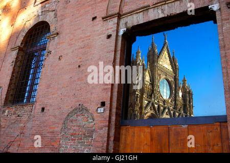 Siena Cathedral or Duomo reflected in a building on the Piazza del Duomo. - Stock Photo