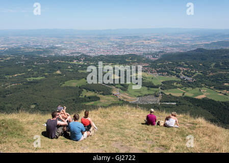 Families sat enjoying the view from the summit of Puy de Dome volcano in the Auvergne region of France - Stock Photo