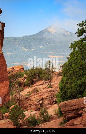 The dramatic red sandstone landscape of the Garden of the Gods in Colorado Springs, CO, USA with Pike's Peak in - Stock Photo