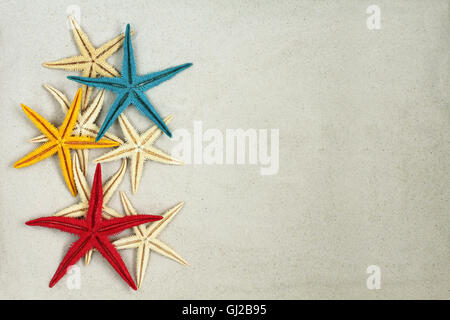 Colorful painted Starfishes on light gray sand - Stock Photo