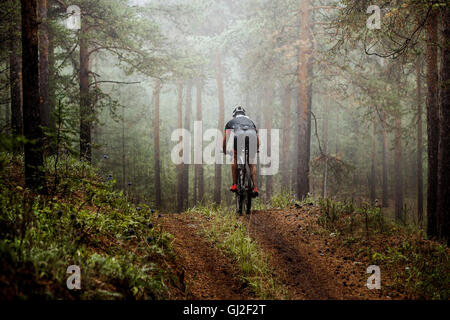 male athlete mountainbiker rides a bicycle along a forest trail. in forest mist, mysterious view - Stock Photo