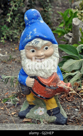 Old weathered garden gnome decoration - Stock Photo
