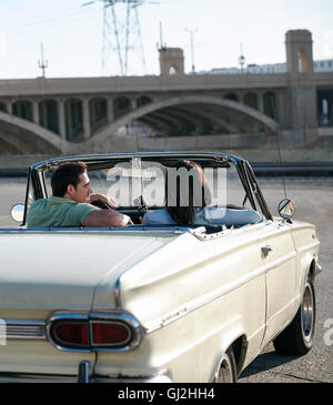 Rear view of couple in convertible classic car, Los Angeles, California, USA - Stock Photo