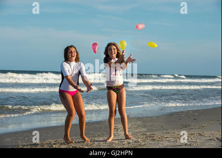 Two young sisters playing with small balloons on beach - Stock Photo