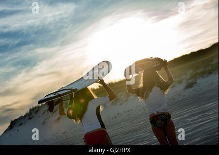 Two young girls in sea, holding surfboards, rear view - Stock Photo