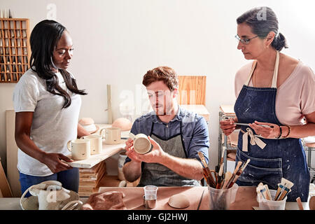 Group of people painting pottery in workshop - Stock Photo