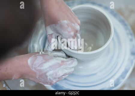 Close up of female potter's hands shaping clay bowl on pottery wheel in workshop - Stock Photo