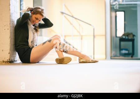 Side view of tattooed woman sitting against wall - Stock Photo