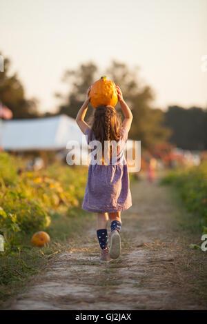 Young girl walking along rural pathway, carrying pumpkin on head, rear view - Stock Photo