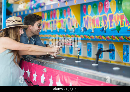 Couple at fairground shooting gallery, Coney island, Brooklyn, New York, USA - Stock Photo
