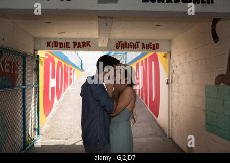 Couple in tunnel kissing, Coney island, Brooklyn, New York, USA - Stock Photo