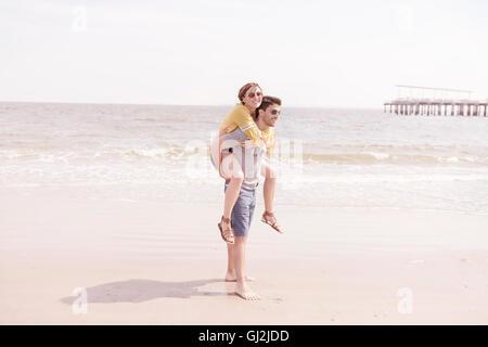 Man on beach giving woman piggyback, Coney island, Brooklyn, New York, USA - Stock Photo
