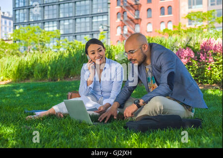 Businessman and woman sitting outdoors on grass, using laptop - Stock Photo