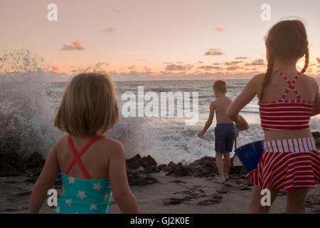 Boy and sisters watching splashing waves at sunrise, Blowing Rocks Preserve, Jupiter Island, Florida, USA - Stock Photo