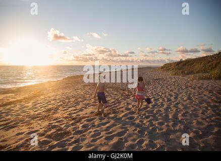 Boy and sister walking along beach at sunrise, Blowing Rocks Preserve, Jupiter Island, Florida, USA - Stock Photo