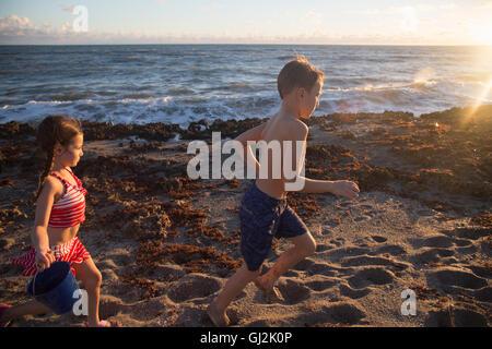 Boy and sister running on beach, Blowing Rocks Preserve, Jupiter Island, Florida, USA - Stock Photo