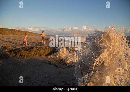 Girl and brother watching ocean waves, Blowing Rocks Preserve, Jupiter Island, Florida, USA - Stock Photo