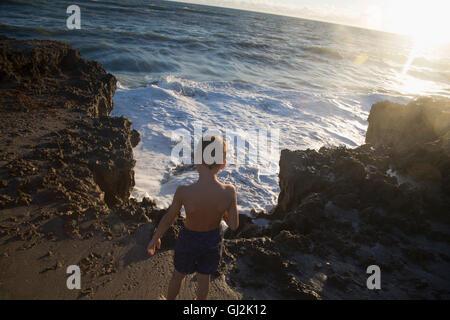 Rear view of boy watching ocean waves, Blowing Rocks Preserve, Jupiter Island, Florida, USA - Stock Photo
