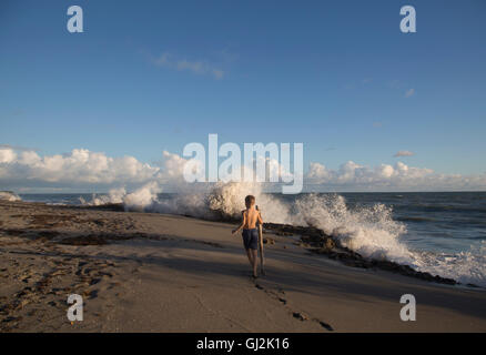 Rear view of boy exploring beach with splashing waves, Blowing Rocks Preserve, Jupiter Island, Florida, USA - Stock Photo