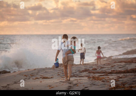Mother carrying daughter on beach at sunrise, Blowing Rocks Preserve, Jupiter Island, Florida, USA - Stock Photo