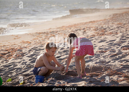 Boy and sister playing with sand on beach, Blowing Rocks Preserve, Jupiter Island, Florida, USA - Stock Photo