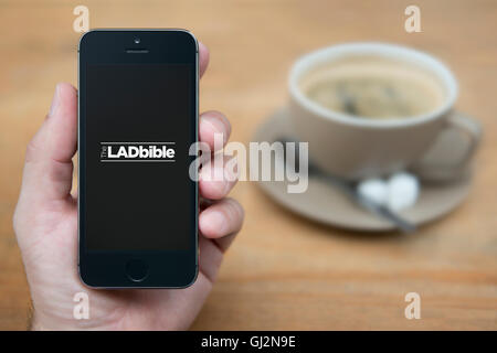 A man looks at his iPhone which displays the Lad Bible logo, while sat with a cup of coffee (Editorial use only). - Stock Photo