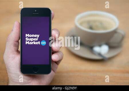 A man looks at his iPhone which displays the Money Supermarket logo, while sat with a cup of coffee (Editorial use - Stock Photo