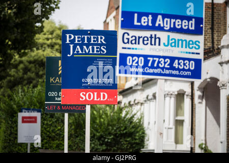 Estate agents boards advertising sale or rental seen outside London property, UK. - Stock Photo