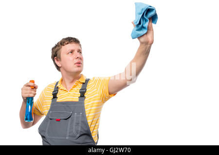 man in a overalls holds a bottle with spray and rag on a white background - Stock Photo