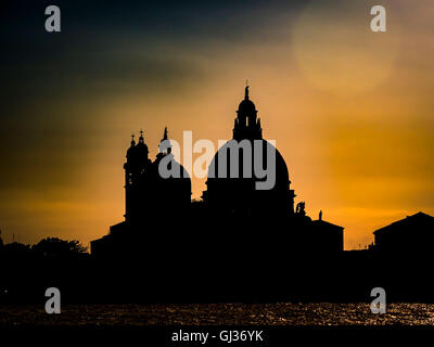 Silhouette of Santa Maria della Salute, Grand Canal, against a golden sky at sunset. Venice, Italy. - Stock Photo
