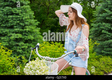 Young girl wearing a beautiful white hat sitting on her bicycle with a bouquet of little white flowers in a basket - Stock Photo