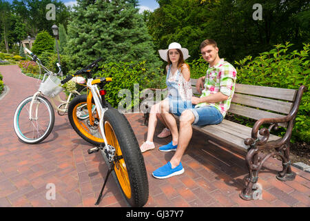 Couple sitting on bench near bikes  parked on brick sidewalk and smiling in beautiful green park - Stock Photo