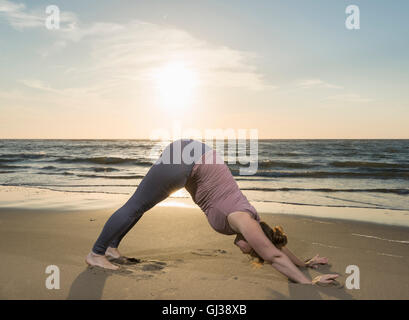 Mature woman practising yoga on a beach at sunset, downward facing dog pose - Stock Photo