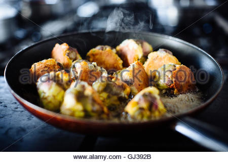 Traditional Italian food preparation, stuffed artichokes with cheese in frying pan, Campania, Italy - Stock Photo