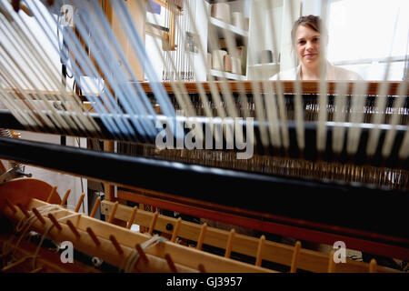 Young woman using loom - Stock Photo