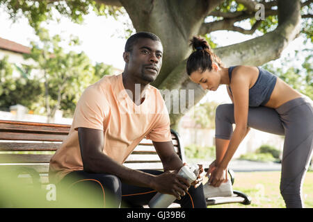 Man wearing sports clothes sitting on park bench looking away - Stock Photo