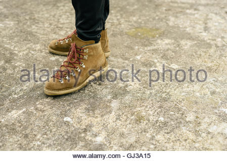 Person wearing boots standing on concrete ground - Stock Photo