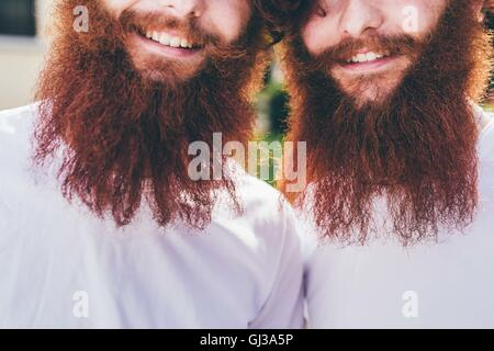 Cropped portrait of young male hipster twins with red beards wearing white tshirts - Stock Photo