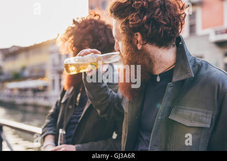 Young male hipster twins with red hair and beards drinking beer on canal waterfront - Stock Photo